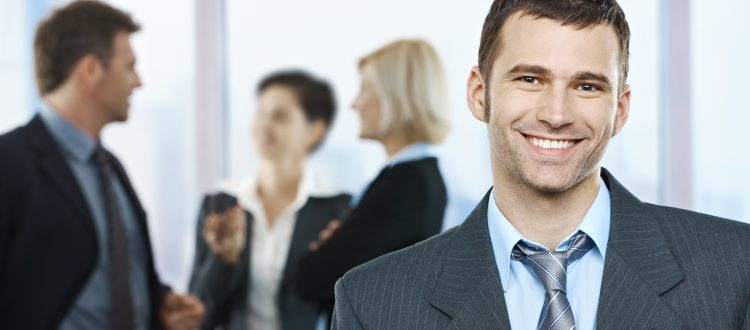 Portrait of happy businessman with coworkers talking in the back